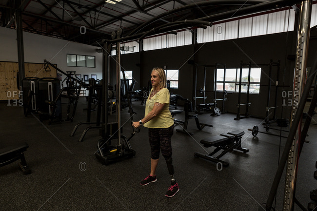Disabled woman exercising on machine in the gym