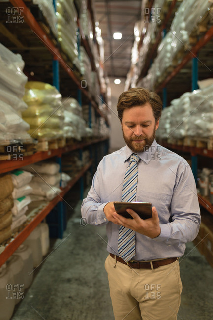 Male manager using digital tablet in warehouse