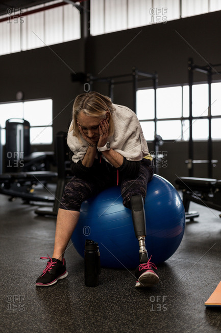 Worried disabled woman sitting on exercise ball in the gym