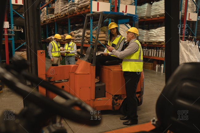 Staff discussing over digital tablet in warehouse