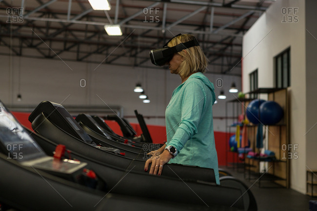 Disabled mature woman using virtual reality headset while exercising on treadmill
