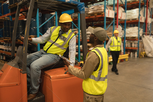 Male workers interacting with each other in warehouse