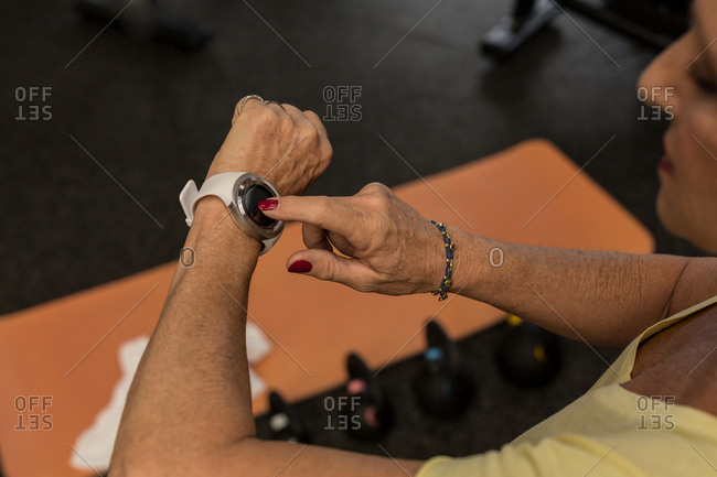 Mid section of woman using smart watch in the gym