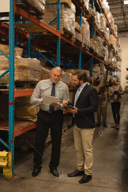 Staff discussing over clipboard in warehouse