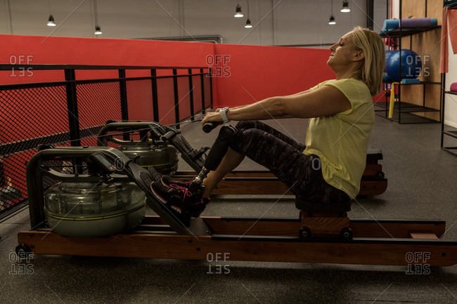 Disabled woman exercising on a machine in the gym