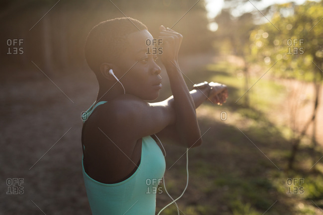 Determined female athlete listening to music while doing morning workout