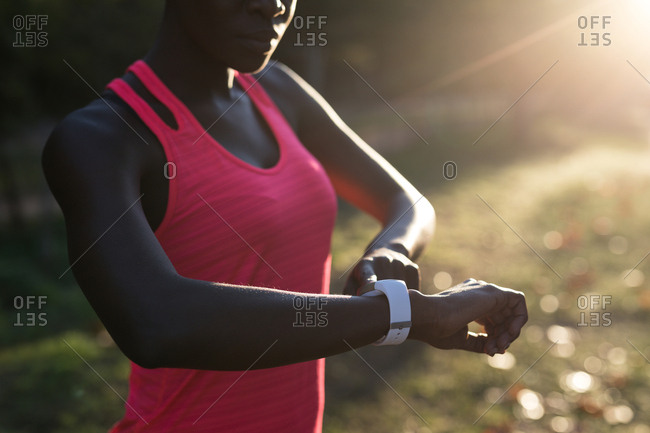 Mid section of female athlete checking her smart watch in the forest