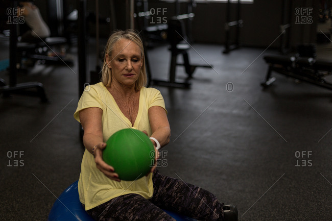 Disabled woman exercising with ball in the gym