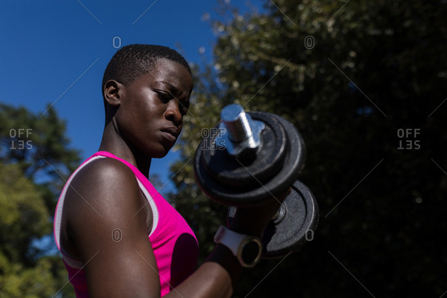 Close-up of female athlete exercising with dumbbell