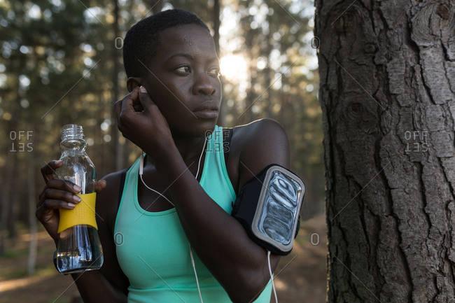 Female athlete with water bottle listening to music in the forest