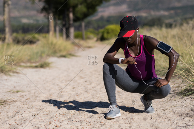 Exhausted female athlete crouching in the forest