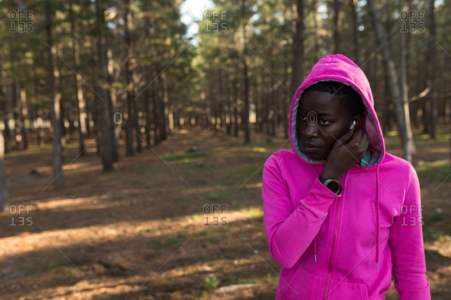 Female athlete in hooded jacket listening to music in the forest