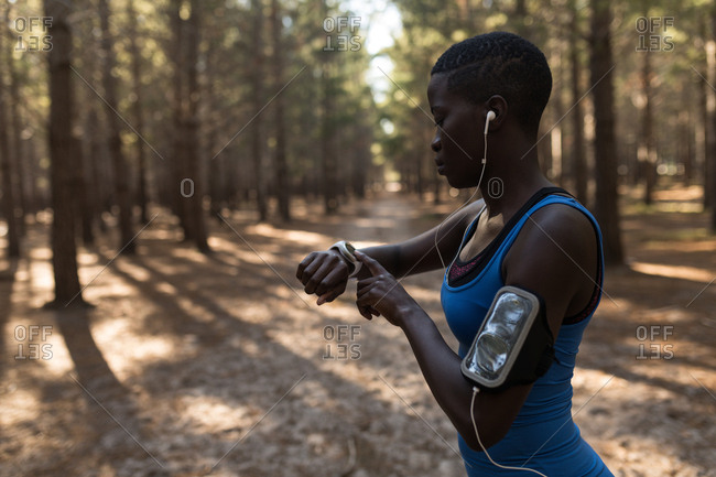 Female athlete checking her smart watch in the forest