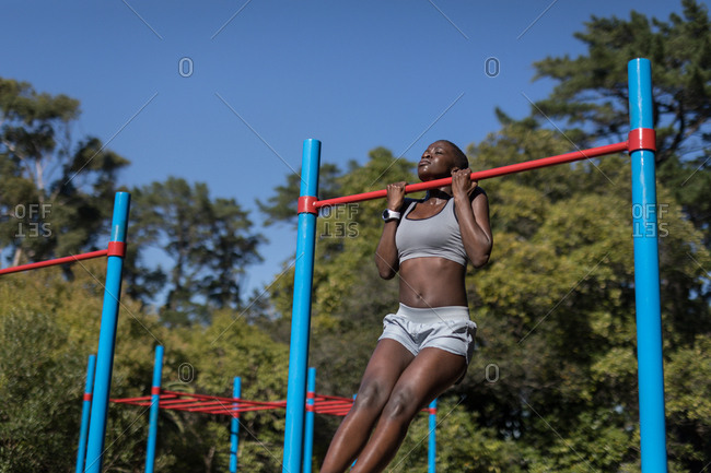 Determined female athlete working out on the bars