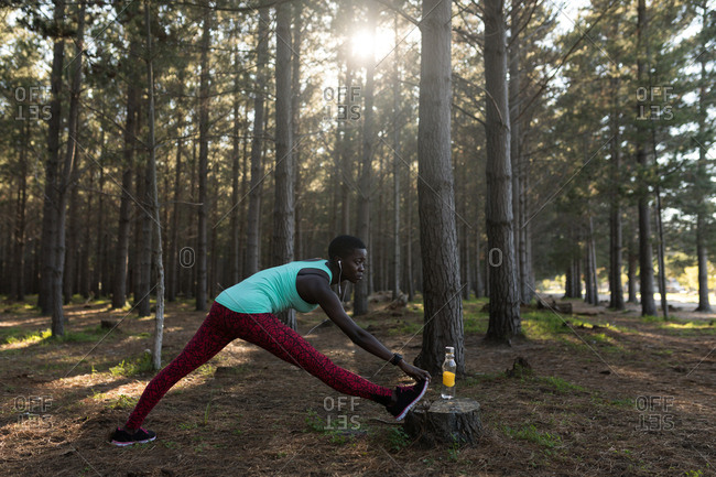 Determined female athlete doing stretching exercise in the forest