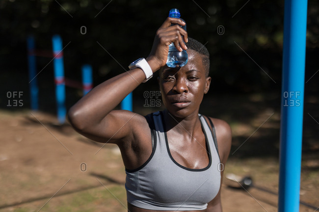 Close-up of exhausted female athlete with water bottle