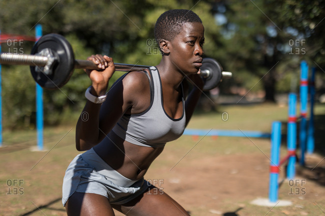 Determined female athlete lifting barbell