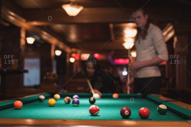 Couple playing snookers in night club