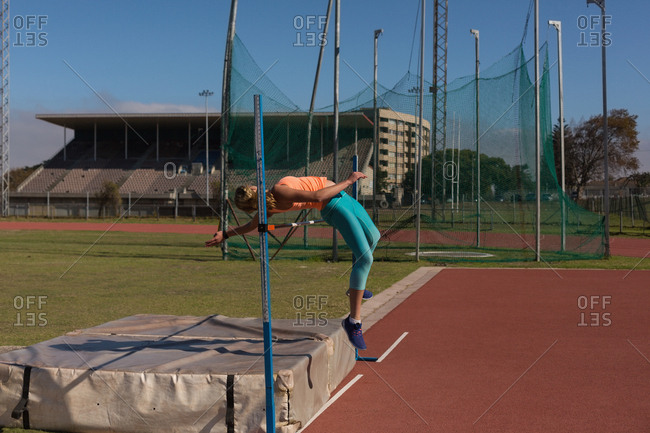 Female athlete practicing high jump at sports venue