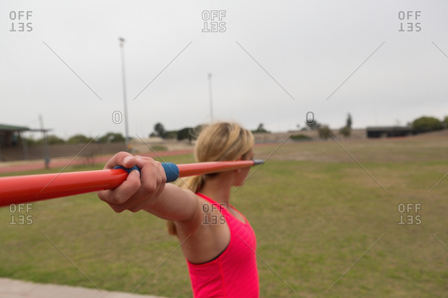 Female athlete practicing javelin throw at sports venue