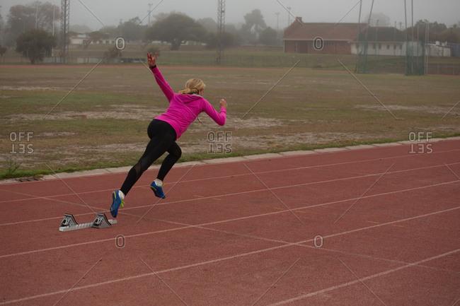 Female athlete running from starting block on the running track