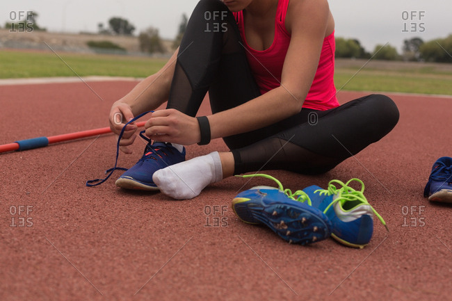 Female athlete tying shoelaces at sports venue