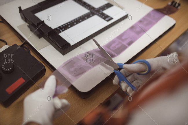 Female photographer cutting filmstrip with photos in photo studio