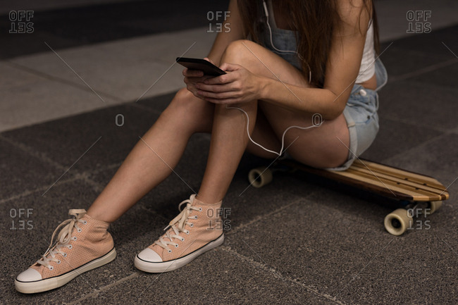 Female skater sitting on skateboard and using mobile phone in the street