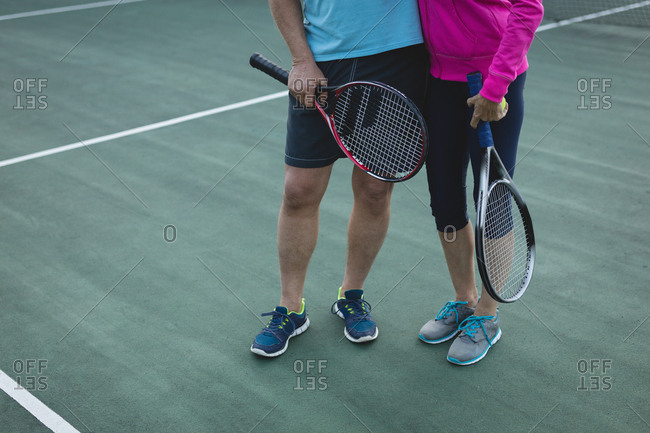 Low section of senior couple standing in tennis court