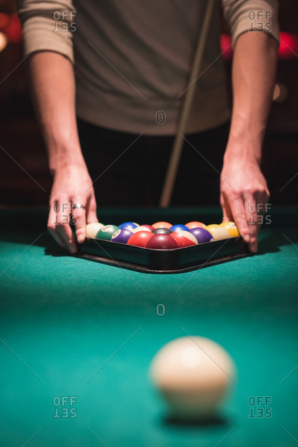 Man arranging snooker balls in triangle rack at night club