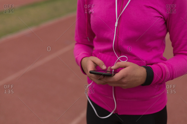 Mid section of female athlete listening music on mobile phone
