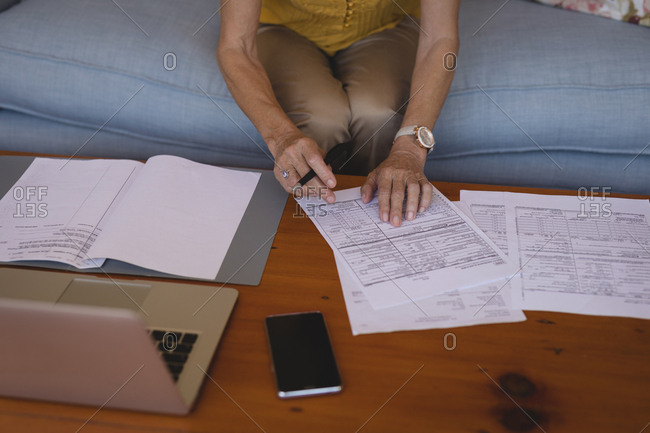 Mid section of senior woman checking bills at home