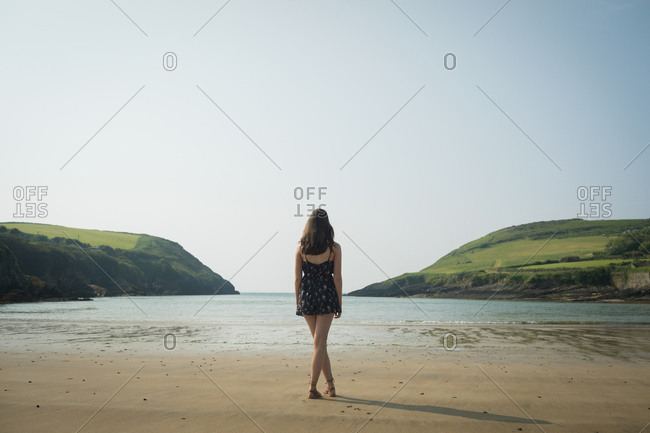 Rear view of woman standing on the beach with her legs crossed