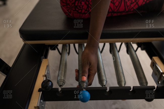 Woman exercising on stretching machine in fitness studio