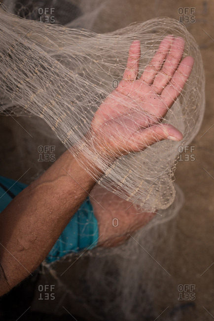 Mid section of fisherman holding fishing net