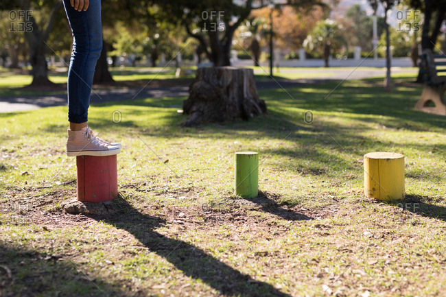 Woman stepping on colorful stumps in the park on a sunny day
