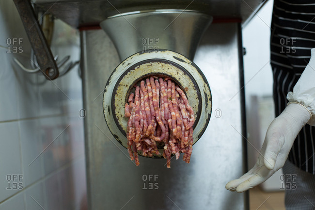 Butcher using machine to minced meat in butcher shop