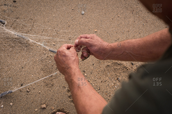 Mid section of fisherman holding fishing net on the beach