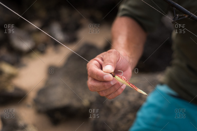 Mid section of fisherman holding fishing tackle