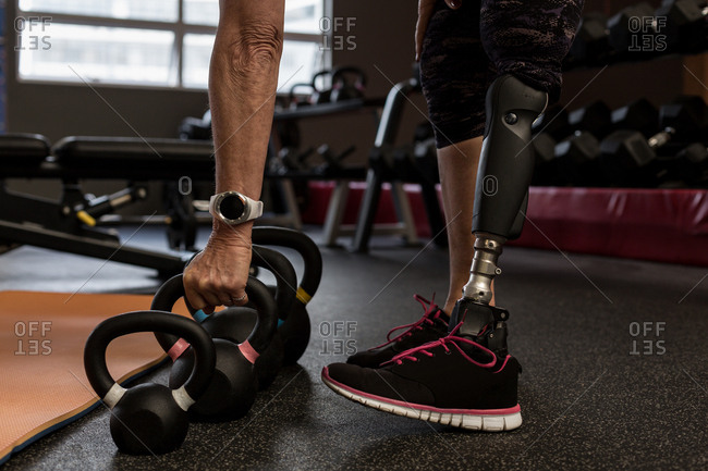 Low section of disabled woman exercising on machine in the gym