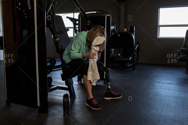 Disabled woman cleaning her face with towel in the gym