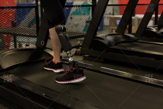 Low section of mature woman exercising on treadmill in the gym