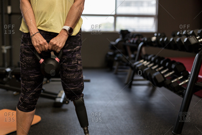 Mid section of disabled woman exercising on machine in the gym