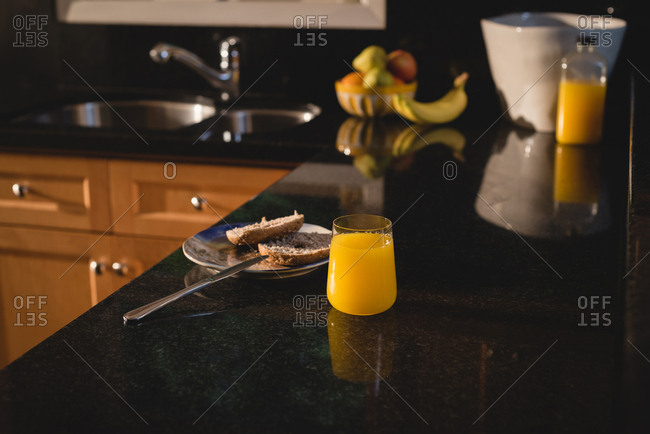 Slice of bread and juice on kitchen worktop at home