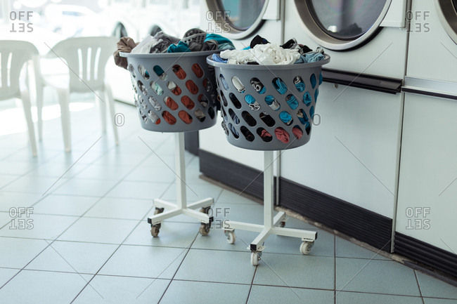 Two laundry baskets near the washing machine at Laundromat