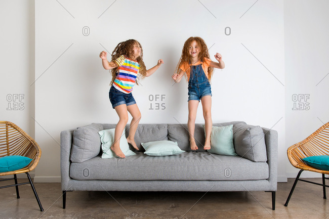 Two girls jumping on gray sofa