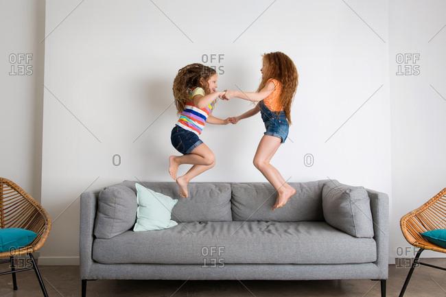Little girls jumping on gray sofa