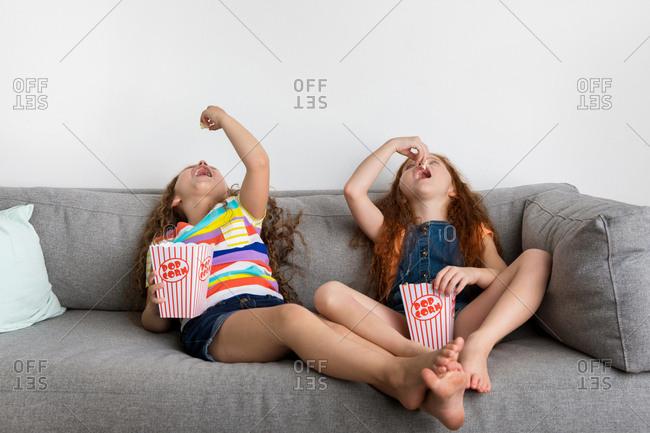 Little girls on gray sofa eating pop corn
