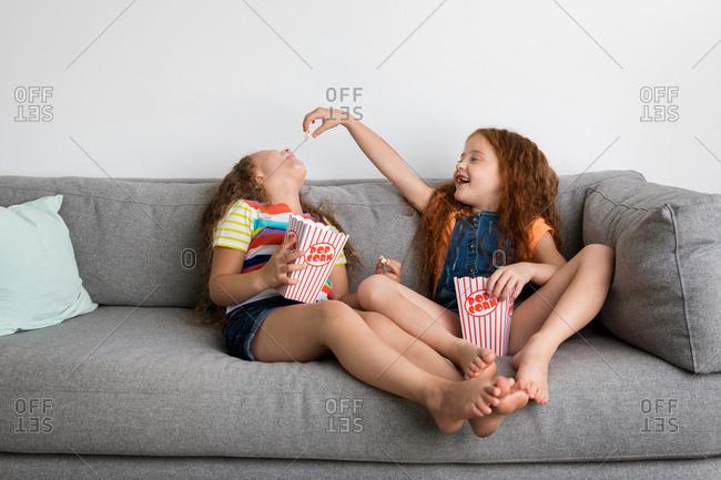 Little girls feeding each other pop corn