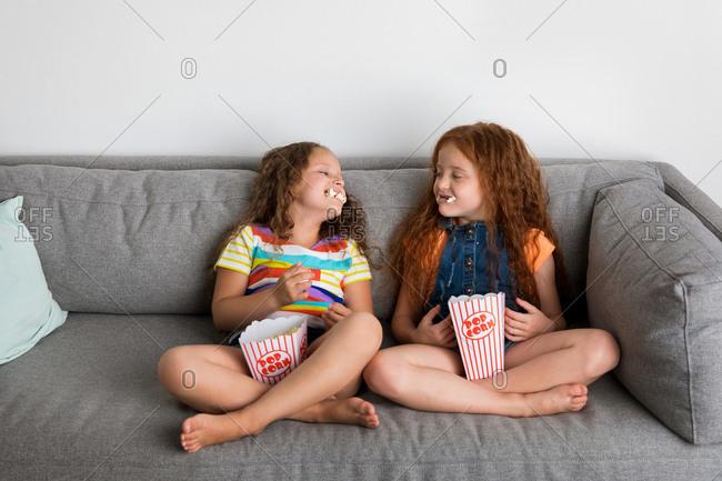 Young girls on gray sofa eating pop corn